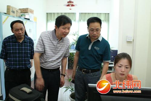 雅安日报传媒集团总编辑,社长杨建光(右二)向何万敏介绍北纬网群建设